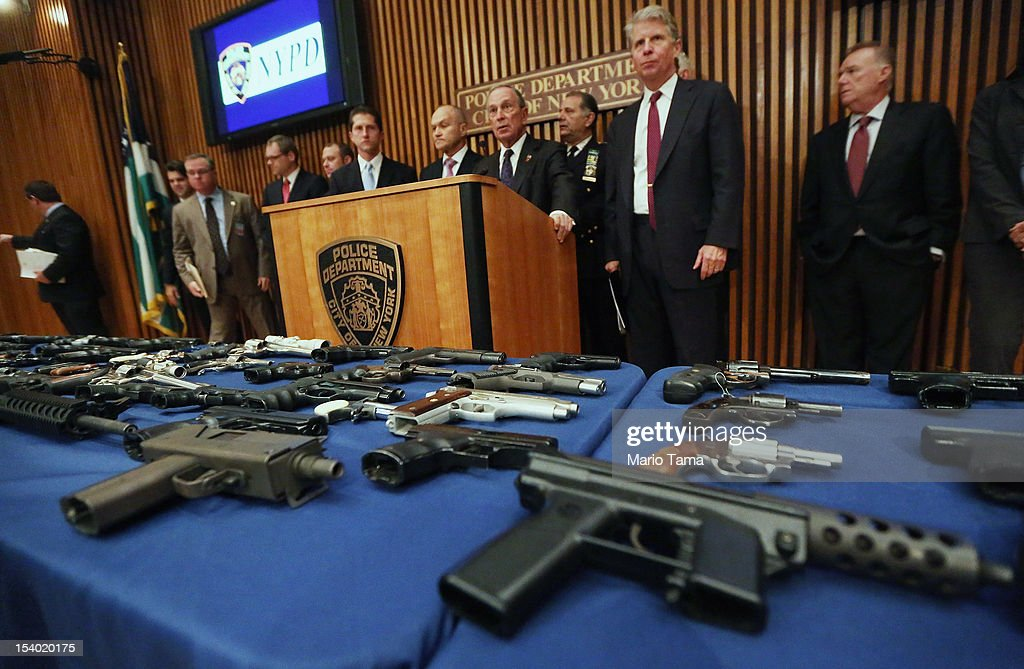 New York City Mayor Michael Bloomberg (4th L) speaks next to other officials above a table of illegal firearms confiscated in a large weapons bust in East Harlem during a press conference on October 12, 2012 in New York City. NYPD detectives arrested 13 suspects for the illegal sale of 129 guns mostly purchased from gun dealers and pawn shops in South Carolina.