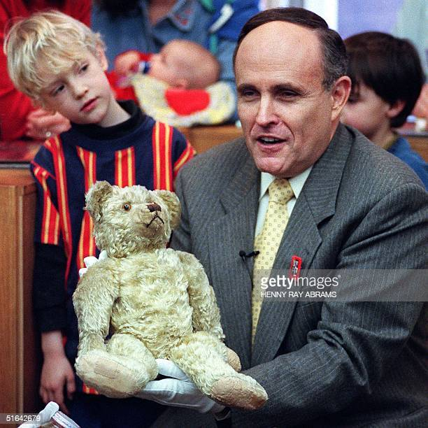 New York City Mayor Rudolph Giuliani holds the original Pooh bear which author A A Milne based his children's books as an unidentified child looks on...