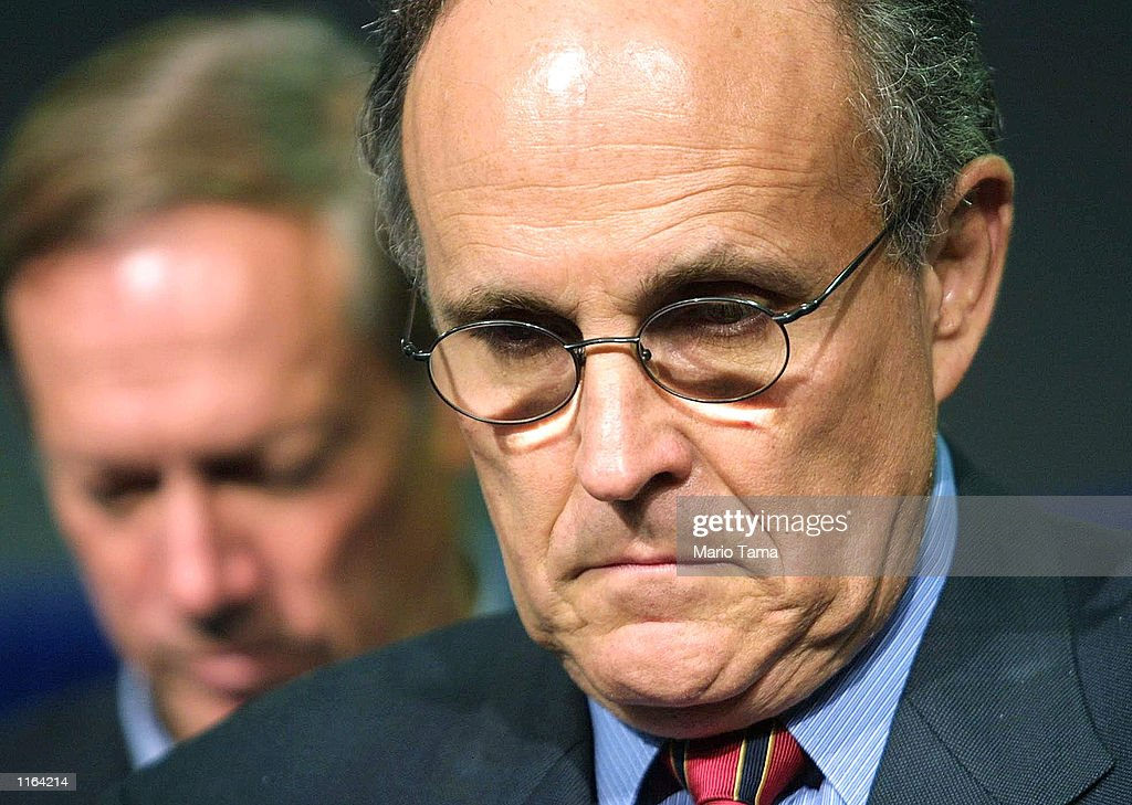 New York City Mayor Rudy Giuliani (R) and Governor George Pataki bow their heads in prayer at the beginning of a press conference September 19, 2001 in New York City. Giuliani said rescue efforts would continue for victims of the attack on the World Trade Center.