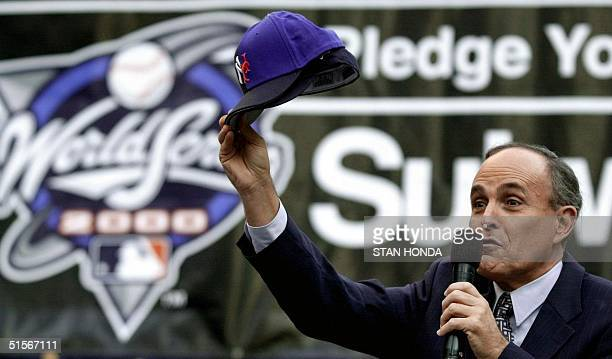 New York City Mayor Rudy Giuliani holds up two baseball hats with the logos of the Yankees and the Mets teams during rally 20 October 2000 at New...