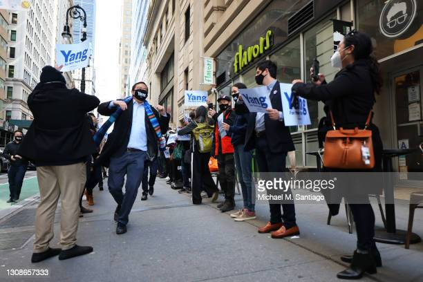 New York City mayoral candidate Andrew Yang elbow bumps supporters as he arrives at the NYC Board of Elections office on March 23, 2021 in New York...