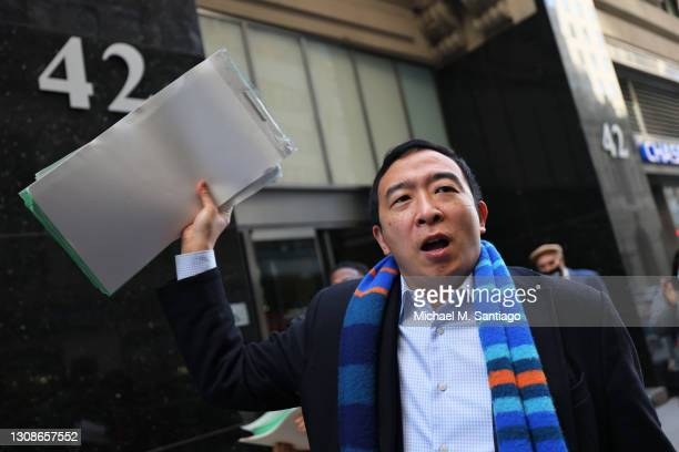 New York City mayoral candidate Andrew Yang holds up his campaign's petition signatures as he speaks outside the NYC Board of Elections office on...
