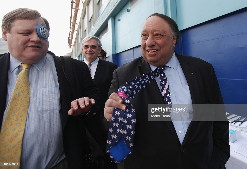 New York City mayoral candidate John Catsimatidis (R) shows off his tie while entering a political forum hosted on a boat in Manhattan on April 9, 2013 in New York City. Six mayoral candidates spoke at the Metropolitan Waterfront Alliance's 2013 Waterfront Conference ahead of the November 2013 mayoral election.