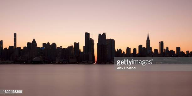usa, ny, new york city, midtown manhattan seen across river at sunset - new york city stock pictures, royalty-free photos & images