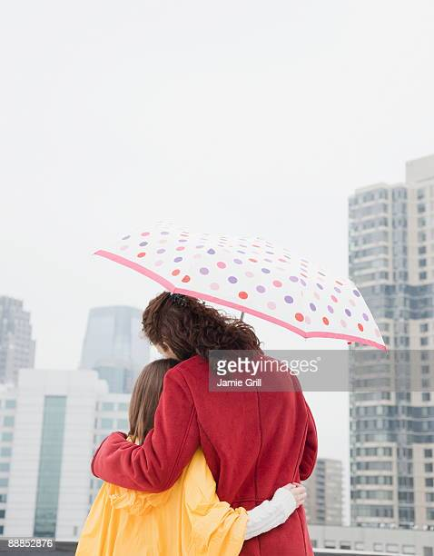 usa, new york city, mother and daughter (10-11 years) embracing under umbrella, rear view - 30 34 years fotografías e imágenes de stock