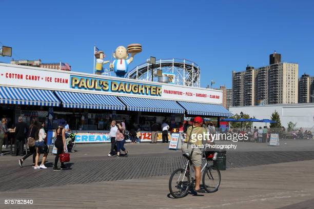 New York City, NY, USA - October 1st, 2017: A senior man riding a bike by the Famous Paul's Daughter restaurant along the boardwalk in Coney Island, Brooklyn