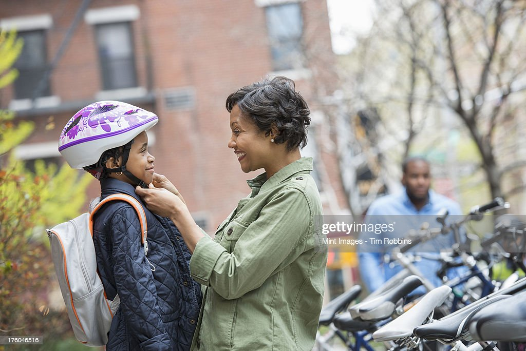 A New York city park in the spring. A boy in a cycle helmet, being fastened by his mother, beside a bicycle rack. : Stock Photo