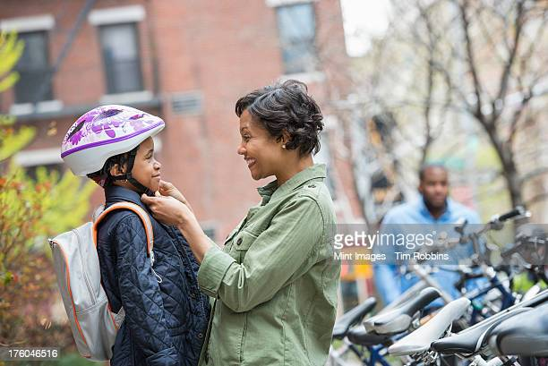 A New York city park in the spring. A boy in a cycle helmet, being fastened by his mother, beside a bicycle rack.