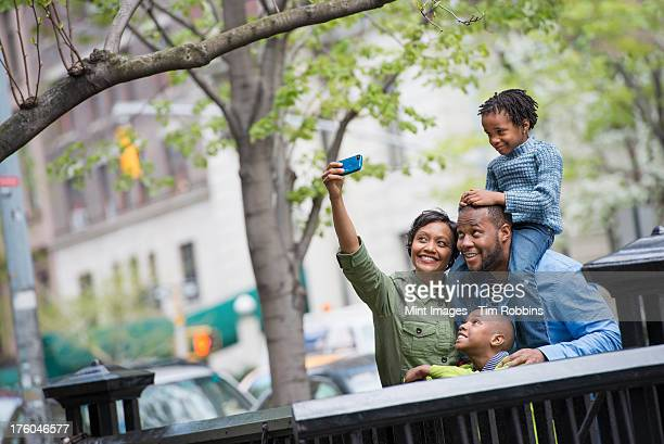A New York city park in the spring. A boy riding on his father's shoulders, and a woman using a smart phone taking a selfy picture.