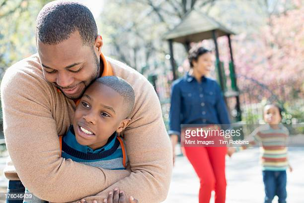 A New York city park in the spring. A family, parents and two boys spending time together. A father hugging his son.