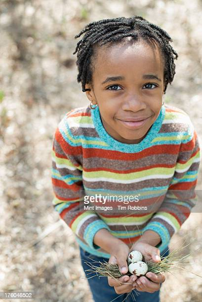 A New York city park in the spring. A small boy in a striped shirt, holding a nest with three birds eggs.