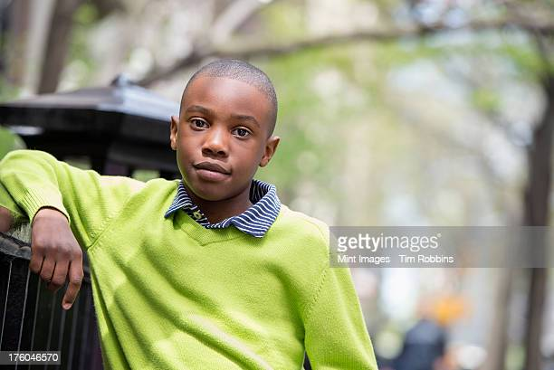 a new york city park in the spring. sunshine and cherry blossom. a boy in a green shirt leaning on a fence. - handsome black boy stock photos and pictures
