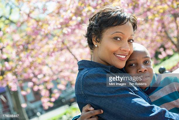 A New York city park in the spring. Sunshine and cherry blossom. A mother and son spending time together.