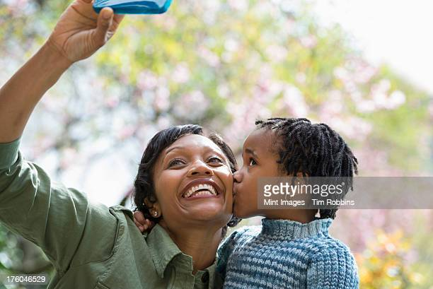 a new york city park in the spring. sunshine and cherry blossom. a mother and son posing for a picture taken using a smart phone. - cherry kiss photos et images de collection