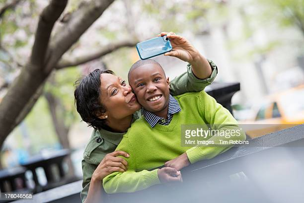 A New York city park in the spring. Sunshine and cherry blossom. A woman taking a picture of herself and her son with a smart phone.