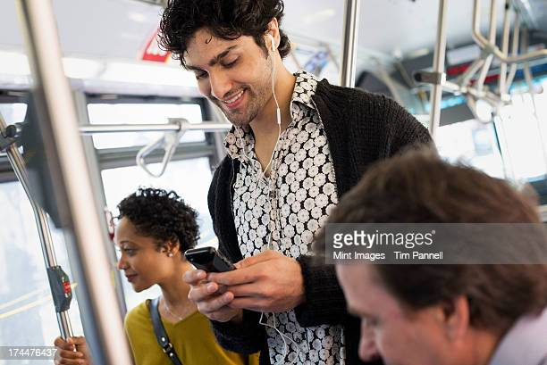 New York City park. People, men and women on a city bus. Public transport. Keeping in touch. A young man checking his cell phone.