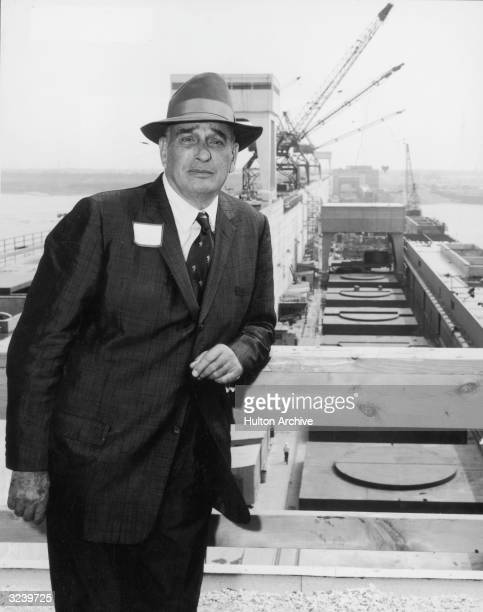 New York City parks commissioner Robert Moses stands and leans on a wooden railing in front of a waterfront project site New York City Winches are...