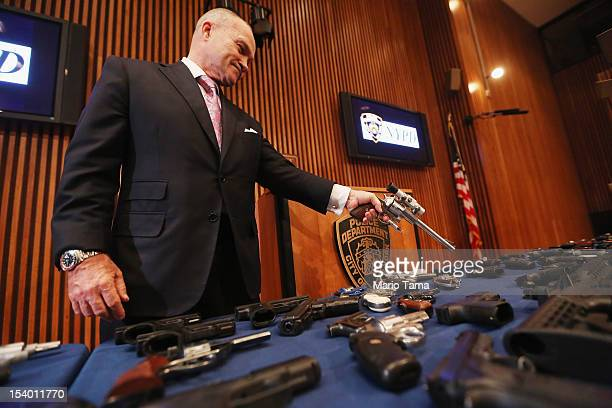 New York City Police Commissioner Ray Kelly displays a confiscated gun above a table of illegal firearms sold to undercover officers in a large...