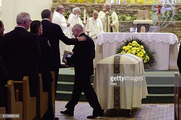 New York City Police Commissioner William Bratton touches the casket of NYPD police officer Brian Moore at the Saint James Roman Catholic Church on...