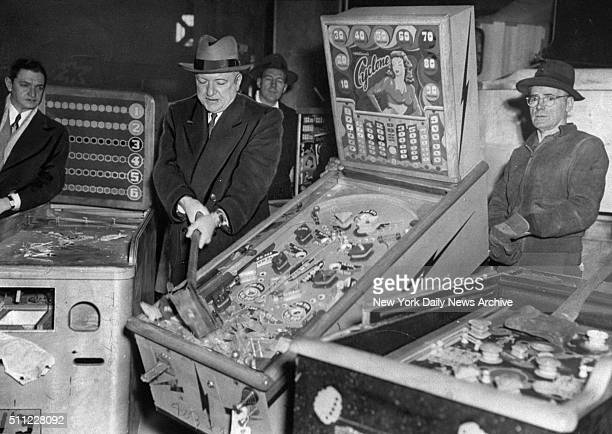 New York City Police Commissioner William P O'Brien smashes illegal pinball machines in a warehouse in the Greenpoint section of Brooklyn
