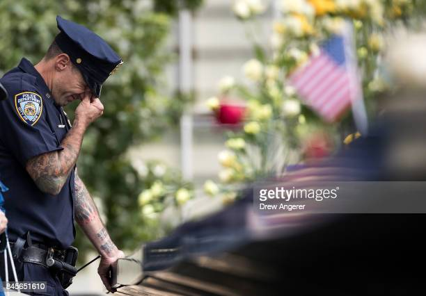 New York City Police Department officer breaks down while visiting the North pool during a commemoration ceremony for the victims of the September 11...