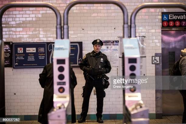 New York City Police Department officer stands watch at the entrance to the Times Square subway station during the evening rush hour December 11 2017...