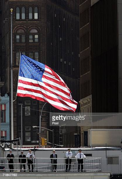 New York City Police Department officers stand below a large American flag at halfmast over ground zero as families gather at the World Trade Center...