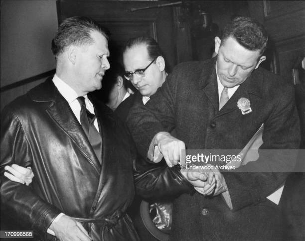 A New York City police detective puts handcuffs on Jimmy Hoffa during on of his arrests New York New York April 1 1962