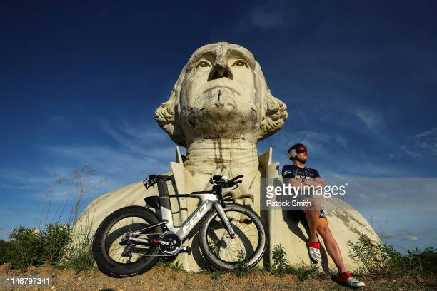 New York City Police officer and triathlete Rob Pollastro poses next to nearly 20feethigh US Presidential bust statues prior to IRONMAN 703 Virginia...