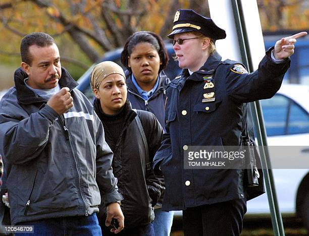 New York City police officer directs an unidentifed man and two women to an emergency center setup for family members of the victims aboard American...