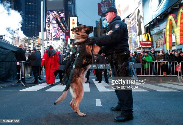 A New York City police officer holds his dog as they patrol in Times Square ahead of New Years events in New York on December 31 2015 Measures to...