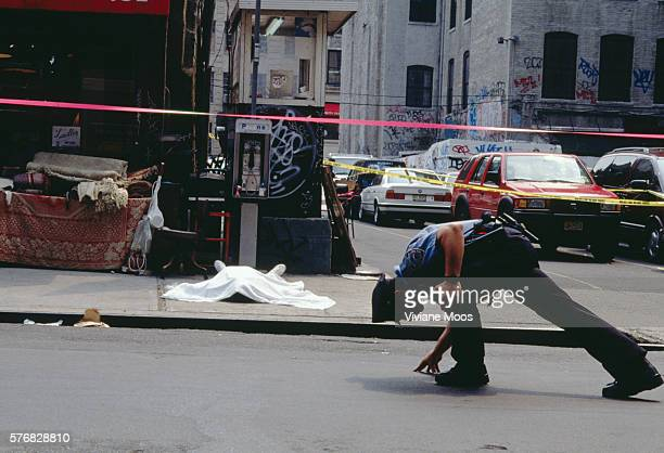 A New York City police officer inspects a crime scene while the body of a murder victim lies on the sidewalk The victim was shot by serial killer...