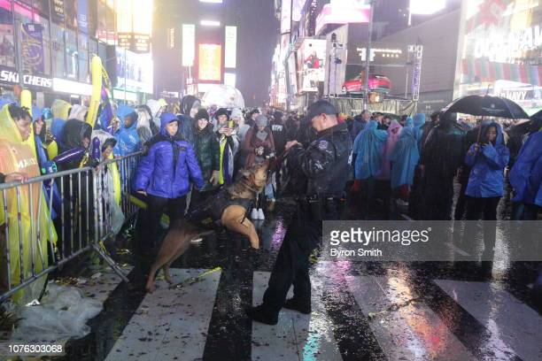A New York City Police officer plays with a K9 Police Dog before the ball drop during New Year's Eve celebrations in Times Square on December 30 2019...