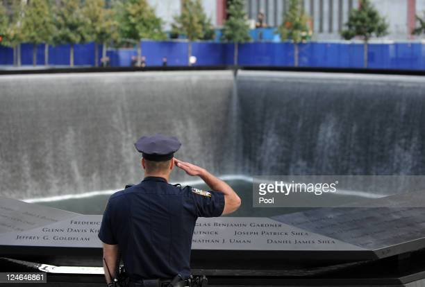 New York City police officer salutes at the North Pool of the 9/11 Memorial during the tenth anniversary ceremonies of the September 11 2001...