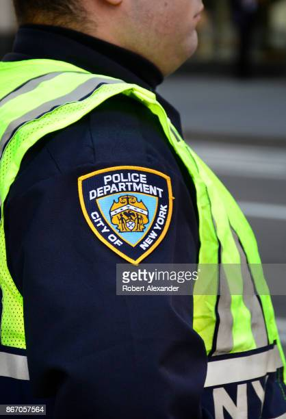 New York City police officer stands at a busy street corner in New York, New York.