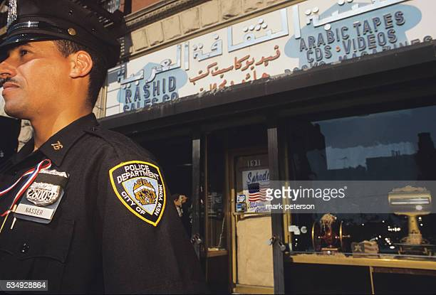 New York City police officer stands guard by Arab community merchants to protect against displaced hostility in the wake of 9/11