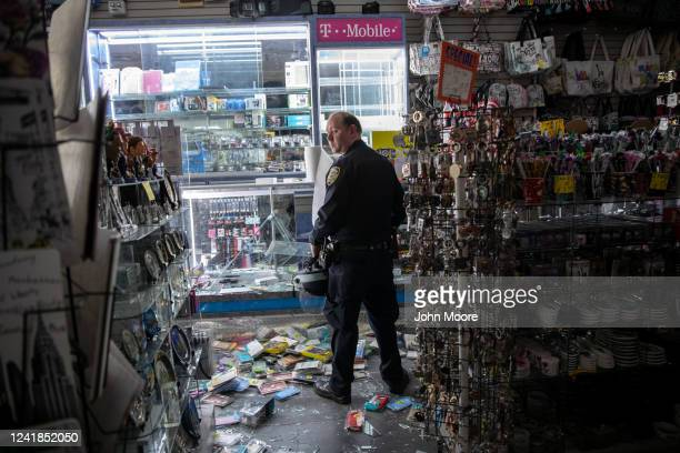New York City police officer stands guard in a looted souvenir and electronics shop near Times Square after a night of protests and vandalism over...