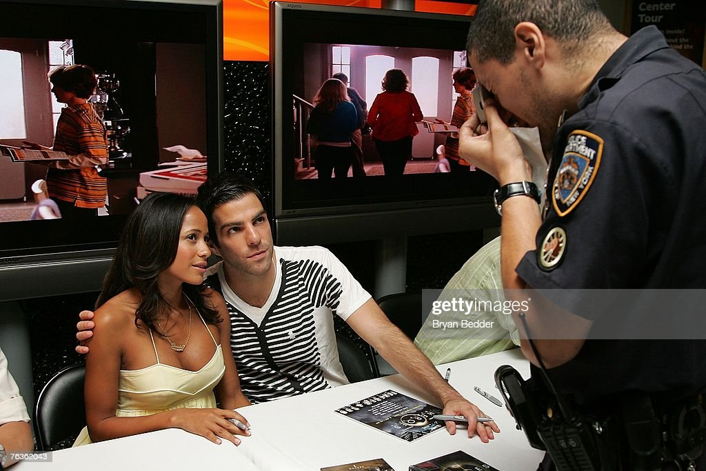 A New York City police officer takes a photo of actors Dania Ramirez and Zachary Quinto at the NBC Universal celabration for the DVD realease of 'Heroes: Season 1' at the NBC Experience store on August 28, 2007 in New York City.