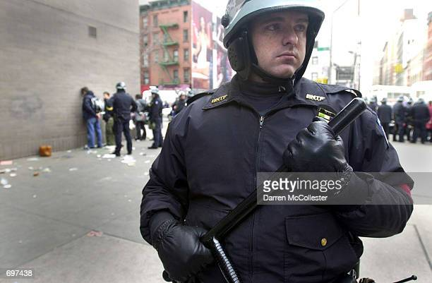 New York City police officer watches the crowd while World Economic Forum protestors stand handcuffed against a wall February 3 2002 after being...