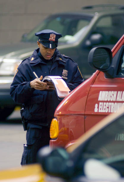 A New York City Police officer writing a parking ticket in Manhattan, NYC.