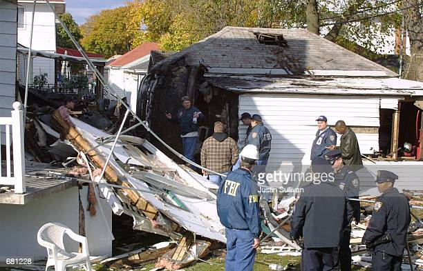 New York City police officers and FBI agents investigate the crash of American Airlines flight 587 November 12, 2001 at one of the houses damages...