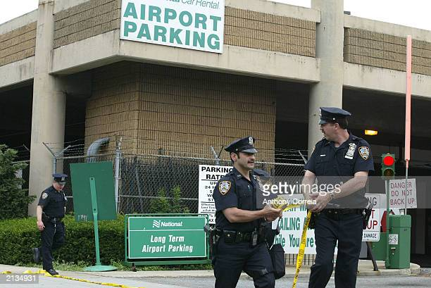 New York City police officers remove caution tape from an area in front of a National car rental office near LaGuardia Airport after a suspicious...