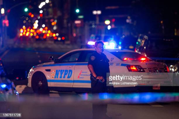 New York City police officers secure and investigate a shooting scene on August 20, 2020 in downtown Brooklyn, New York. Two men got into a fight and...