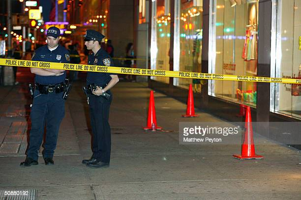New York City Police officers stand at the scene of a shooting on Sixth Avenue between 47th and 48th streets May 20 2004 in New York City The...