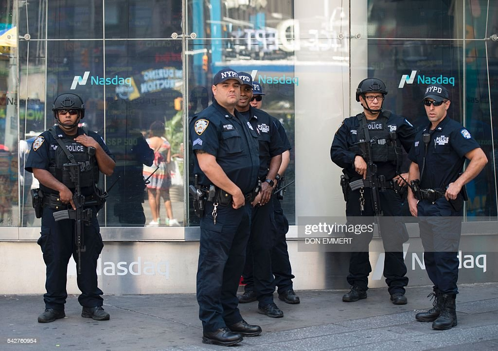 New York City police officers stand on duty outside the Nasdaq offices in Times Square on June 24, 2016 in New York. US stocks tumbled early Friday, with banking equities suffering especially deep losses, joining an international rout after Britain's surprise vote to exit the European Union. The Dow sank more than 500 points shortly after the markets opened at 1330 GMT, but then quickly recovered some of the losses. The selloffs in the US were smaller than in many overseas markets. EMMERT