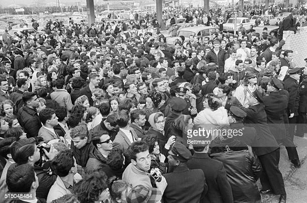 New York City police officers try their best to contain several hundred Beatles fans who have arrived at Idlewild Airport some from hundreds of miles...