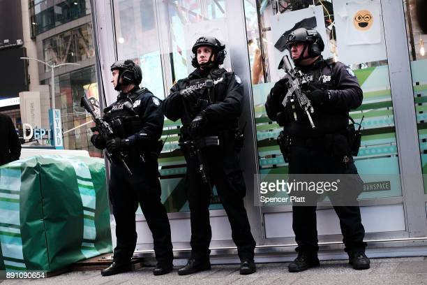 New York City police stand on a corner in Times Square a day after a man prematurely detonated a suicide bomb in nearby Port Authority Bus Terminal...