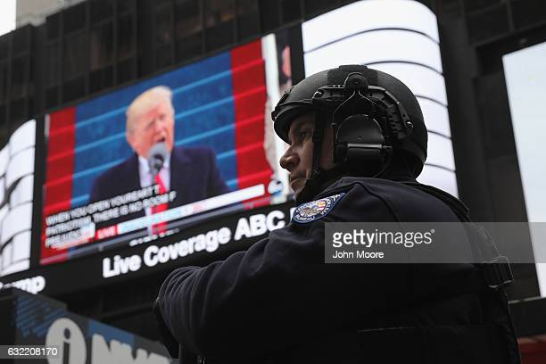 New York City policeman stands guard during the televised inauguration of Donald Trump as the 45th President of the United States while in Times...