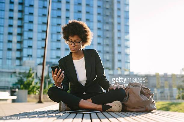 usa, new york city, portrait businesswoman looking at smartphone - black blazer stock pictures, royalty-free photos & images