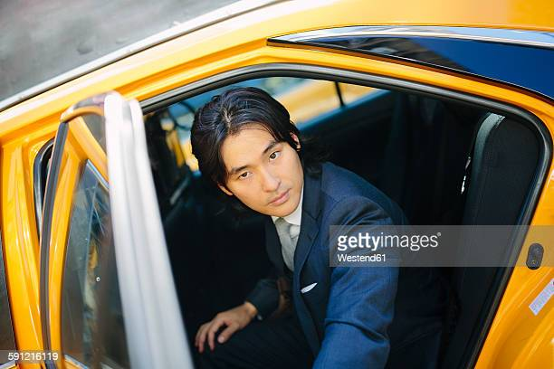 usa, new york city, portrait of businessman entering a taxi - イエローキャブ ストックフォトと画像
